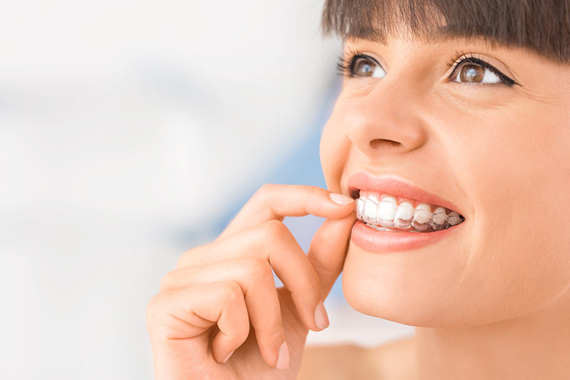 woman-using-invisalign-invisalign-dentist-in-coral-gables-florida
